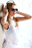 Wet music. Wet babe in white shirt and sunglasses listening for the music using headphones Royalty Free Stock Images