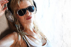 Wet music. Wet babe in white shirt and sunglasses listening for the music using headphones Stock Photography