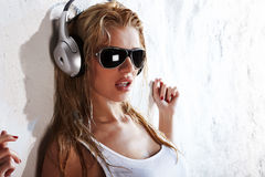 Wet music. Wet woman in white shirt and sunglasses listening for the music using headphones Royalty Free Stock Images