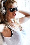 Wet music. Wet woman in white shirt and sunglasses listening for the music using headphones Royalty Free Stock Photos