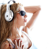 Wet music. Wet woman in white shirt and sunglasses listening for the music using headphones Stock Image