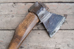 Wet old axe lying on a dark wooden surface Stock Photos