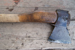 Wet old axe lying on a dark wooden surface Stock Image