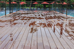 Wet outdoor decking beside swimming pool after raining Stock Images