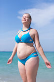 Wet overweight middle aged woman in blue bikini. Wet overweight middle aged woman at the sea. Wet overweight woman in blue bikini standing with eyes closed and Royalty Free Stock Photo