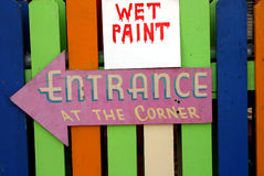 Wet Paint. A sign warns of a newly painted fence and another sign directs customers to the entrance Stock Photography