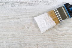Wet paint brush ready to apply paint on old boards Stock Photos