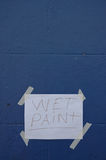 Wet Paint paper sign on blue wall Stock Photos