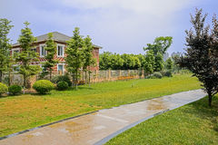 Wet path in irrigated lawn before fenced house on sunny summer d Stock Images