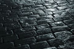 Wet pavement. Of rectangular blocks by night alight by streetlight. Landscape orientation stock photos