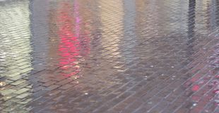 Wet pavement reflecting lights. Pavement of a pedestrian zone in city at rainy day reflecting illumination of shop windows Stock Images