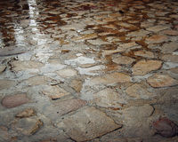 Wet paving stone with puddles - vintage effect. Yard paving stones. Stock Photo