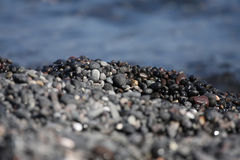 Wet pebbles on the sea. Kamari Beach, Santorini Stock Photos