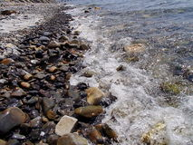 Wet pebbles in the sea. Sea surf. Summer, august. South Ozereyevka, Novorossiysk, Russia. Stock Image