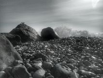 Peacefull seashore. Wet pebbles seashore, deserted beach with nobody, special place for rest and meditation, grayscale photo with dramatic tone Royalty Free Stock Images