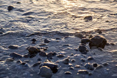 Wet pebbles at the sunset Stock Images