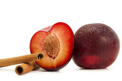 Wet plum and a half and two cinnamon sticks Royalty Free Stock Photography