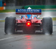 Wet Race. ASSEN, NETHERLANDS - OCTOBER 19, 2014: Formula A1 car with rain tires leaving a spray of water behind when leaving the pits lane during a wet race Stock Images