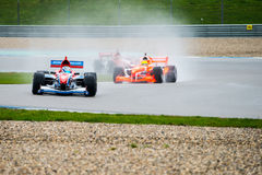 Wet Race for FA1 Cars. ASSEN, NETHERLANDS - OCTOBER 19, 2014: Team Great Britain in the lead, followed by Team Holland during the final race of the Formula A1 GP stock photo