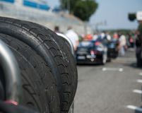 Wet racing tire set motor sport. Wet racing tire set on race starting line with car out of focus in background royalty free stock images