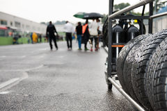 Wet racing tire set motor sport. Wet racing tire set on race starting line with mechanics out of focus in background stock image