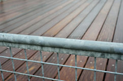 Wet railing of the wooden footway. The wet metal banisters of the batten platform are photographed closely Royalty Free Stock Photography