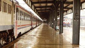 Wet railway station platform with train carriages standing in background - Transportation - Weather stock video footage