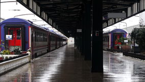 Wet railway station platform with train carriages standing in background - Transportation - Weather stock footage