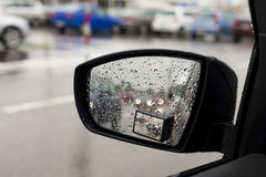 Wet by the rain the car mirror, blurry cars in mirror. Stock Image