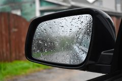 Wet from the rain the mirror of the car close up stock photography