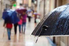 Wet rain umbrella in front of out of focus people Stock Photos