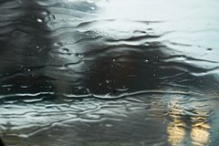 Wet rainy grey wallpaper. Rain drops on the windshield of the car in autumn time stock photos