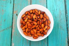 Wet raw almonds on turquoise wooden table Stock Images