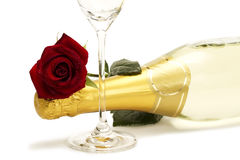 Wet red rose on a champagne bottle behind a champa. Gne glass on white background Stock Photo