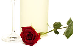 Wet red rose in front of a prosecco bottle and a c. Wet red rose in front of a dull prosecco bottle and the bottom of a champagne glass on white background Royalty Free Stock Photography