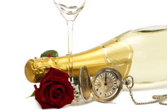 Wet red rose under a champagne bottle with a old p. Ocket watch and a empty champagne glass on white background Royalty Free Stock Photos