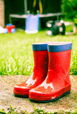 Wet red wellies. A pair of red children's wellies outside in a garden wet weather with garden toys in the background Stock Photography