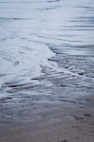 Wet rippled sand and water at the beach abstract background Stock Images