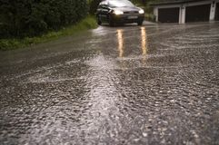 On a wet road. Reflections on aspalt after heavy shower with car in background Stock Image