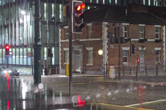 Wet road and buildings in night time in Manchester City, England Stock Image