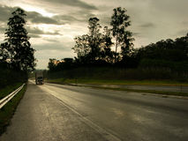 Wet road by dusk. With white truck driving up hill Stock Photo