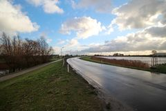 Wet road on the dylke  along river Hollandse IJssel in Nieuwerkerk aan den IJssel in the Netherlands. Wet road on the dylke along river Hollandse IJssel in Stock Image