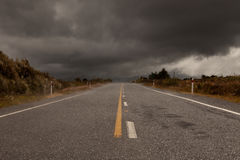 Wet road leading into a storm Stock Images