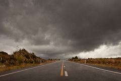 Wet road leading into a storm cloudy sky Royalty Free Stock Images