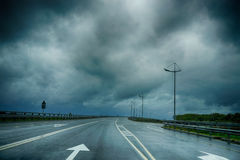 Wet road markings under a dark stormy Royalty Free Stock Images