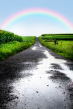 Wet Road Rainbow. Wet road after rain in rural farm area with rainbow Royalty Free Stock Photography