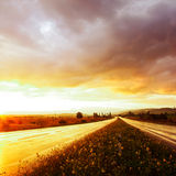 Wet road and sky. Wet road after rain and sunset over fields Stock Photo