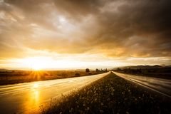Wet road and sky. Wet road after rain and sunset over fields Royalty Free Stock Image