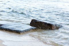Wet rocks being washed by waves of the sea. During day in singapore Royalty Free Stock Photography