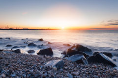 Wet Rocks. Sunrise with Intense Colours and Wet Rocks on a Beach Royalty Free Stock Images